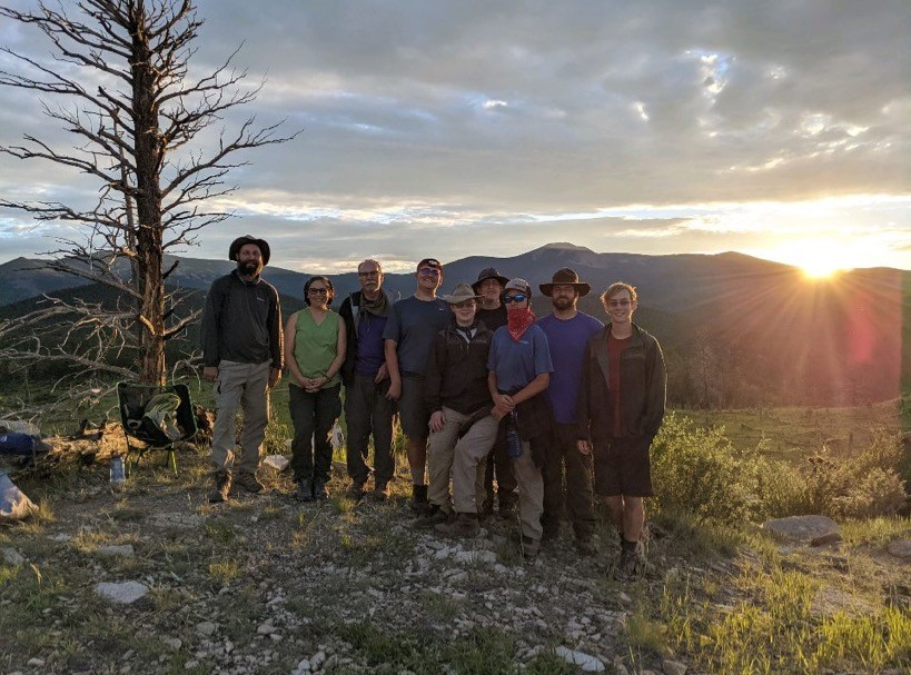 Boy Scouts Troop 152 at Philmont Scout Ranch in New Mexico standing with mountain landscape at sunset